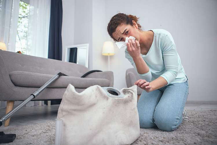 woman sneezing because she is not use the correct dusting techniques to clean dust without spreading it